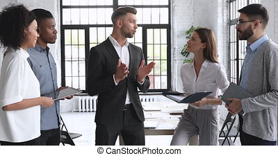 Confident businessman leader coach mentor boss wear suit giving instructions talking to happy diverse sales team business people in office explaining project plan at corporate group stand up meeting