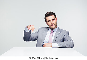Confident businessman pointing finger down