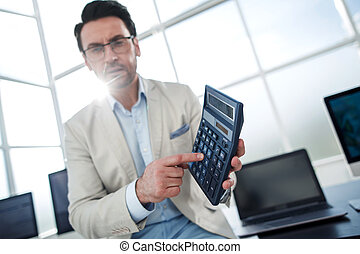 confident businessman pointing to calculator