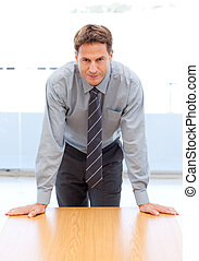 Confident businessman posing leaning on a table in an office