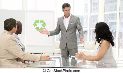 Confident businessman presenting recycling sign in the...