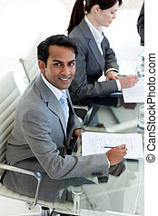 Confident businessman sitting at a conference table