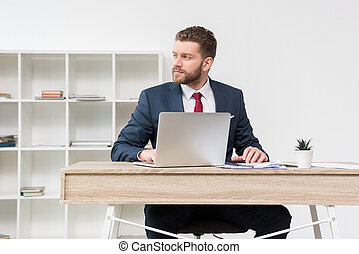 Confident businessman sitting at table with laptop in office