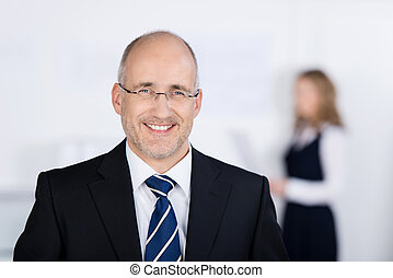 Portrait of confident businessman smiling with coworker in background at office