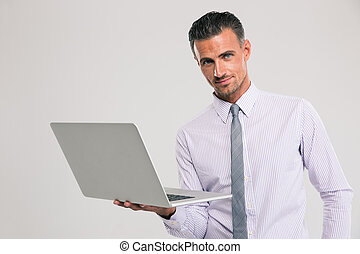 Confident businessman standing with laptop computer