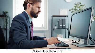 Confident businessman using computer for work at office - ...