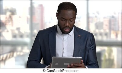 Confident businessman using digital tablet.