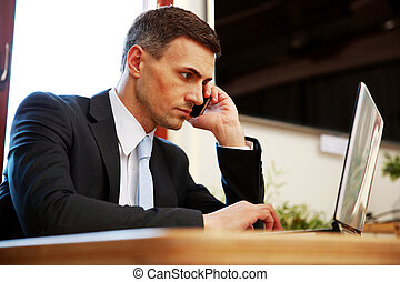 Confident businessman using laptop and talking on the phone at office
