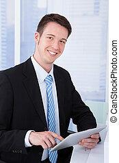 Confident Businessman Using Tablet Computer At Desk