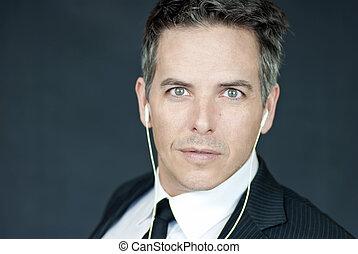 Confident Businessman Wearing Headphones Looks To Camera