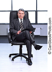 confident businessman with a leather folder, sitting in the office