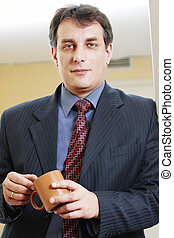 Confident businessman with cup