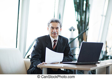 Confident businessman with documents on a laptop