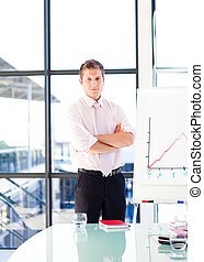 Confident businessman with folded arms in a presentation