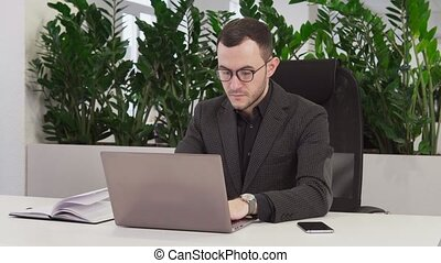 Confident businessman with glasses using a laptop
