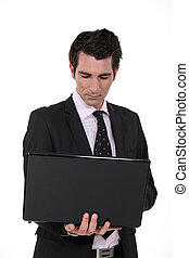 Confident businessman with laptop computer