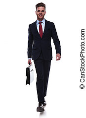 confident businessman with suitcase in hand stepping
