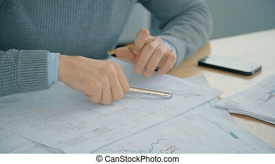 Confident businessman working with start up project, writing at table in modern office.