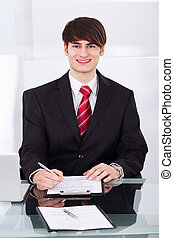 Confident Businessman Writing On Paper At Desk