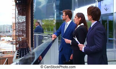 Confident businesspersons talking in front of modern office...
