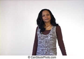 A young confident businesswoman moves around and smiles at the camera. Shot with fixed focus from a tripod on mini DV.