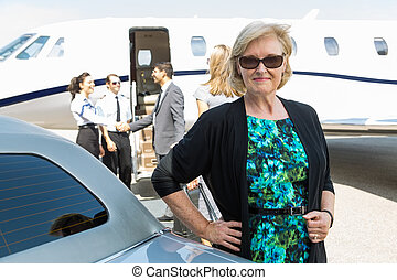 Confident Businesswoman Against Private Jet