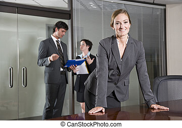 Confident businesswoman, colleagues in background