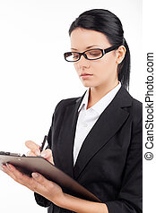Confident businesswoman. Confident young business woman writing something in her note pad while standing isolated on white
