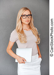 Confident businesswoman. Confident young woman holding digital tablet and looking at camera while standing against white background
