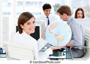 Confident businesswoman holding a globe