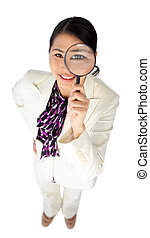 Confident businesswoman holding a magnifying glass