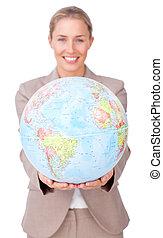 Confident businesswoman holding a terrestrial globe