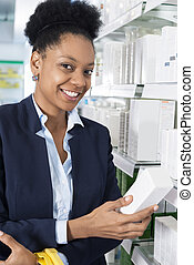 Confident Businesswoman Holding Medicine Packet In Pharmacy