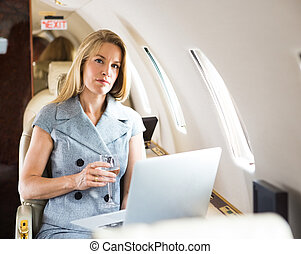 Confident Businesswoman Holding Wineglass In Private Jet - ...