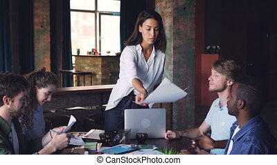 Confident businesswoman is giving papers with visual...
