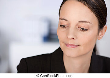 Confident Businesswoman Looking Down In Office