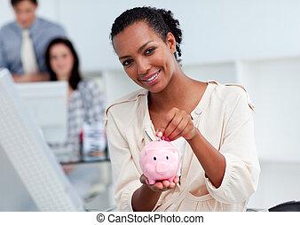 Confident businesswoman saving money in a piggy-bank at her ...