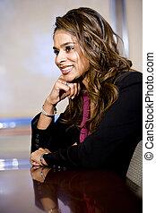 Confident businesswoman sitting in boardroom