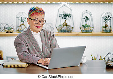 Confident businesswoman sitting with laptop