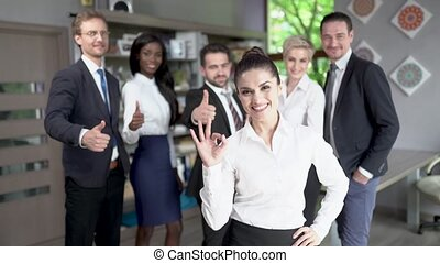 Confident businesswoman standing in front of her successful team