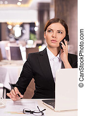 Confident businesswoman. Thoughtful young woman in formalwear talking on the phone and looking away while sitting at the restaurant