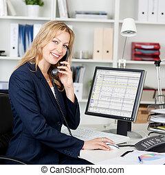 Confident Businesswoman Using Landline Phone At Desk - ...