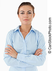 Confident businesswoman with arms folded against a white ...