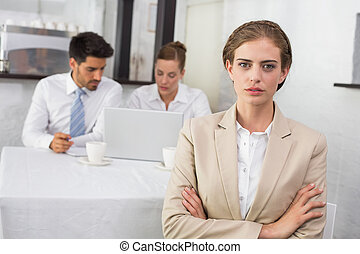 Confident businesswoman with colleagues at office desk