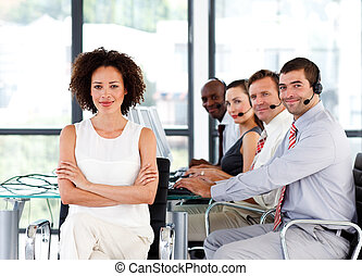 Confident businesswoman with folded arms in a call center