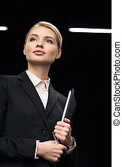 confident businesswoman with notepad in hand isolated on black