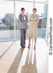 Confident businesswomen standing in bright office