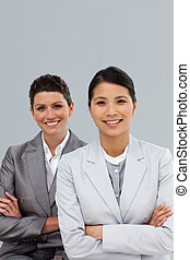 Confident businesswomen with folded arms standing