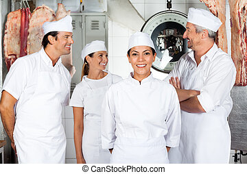 Confident Butcher With Colleagues In Butchery