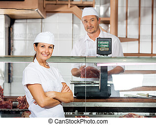 Confident Butcher With Male Colleague Weighing Meat